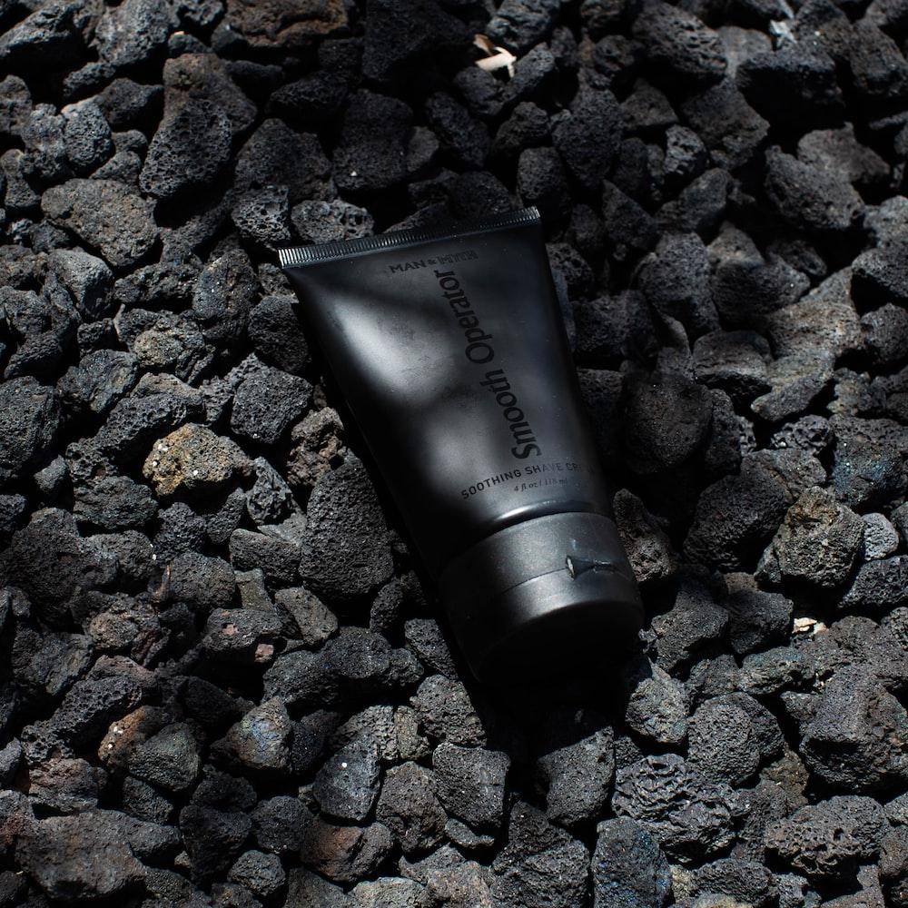 black tube bottle on gray stones
