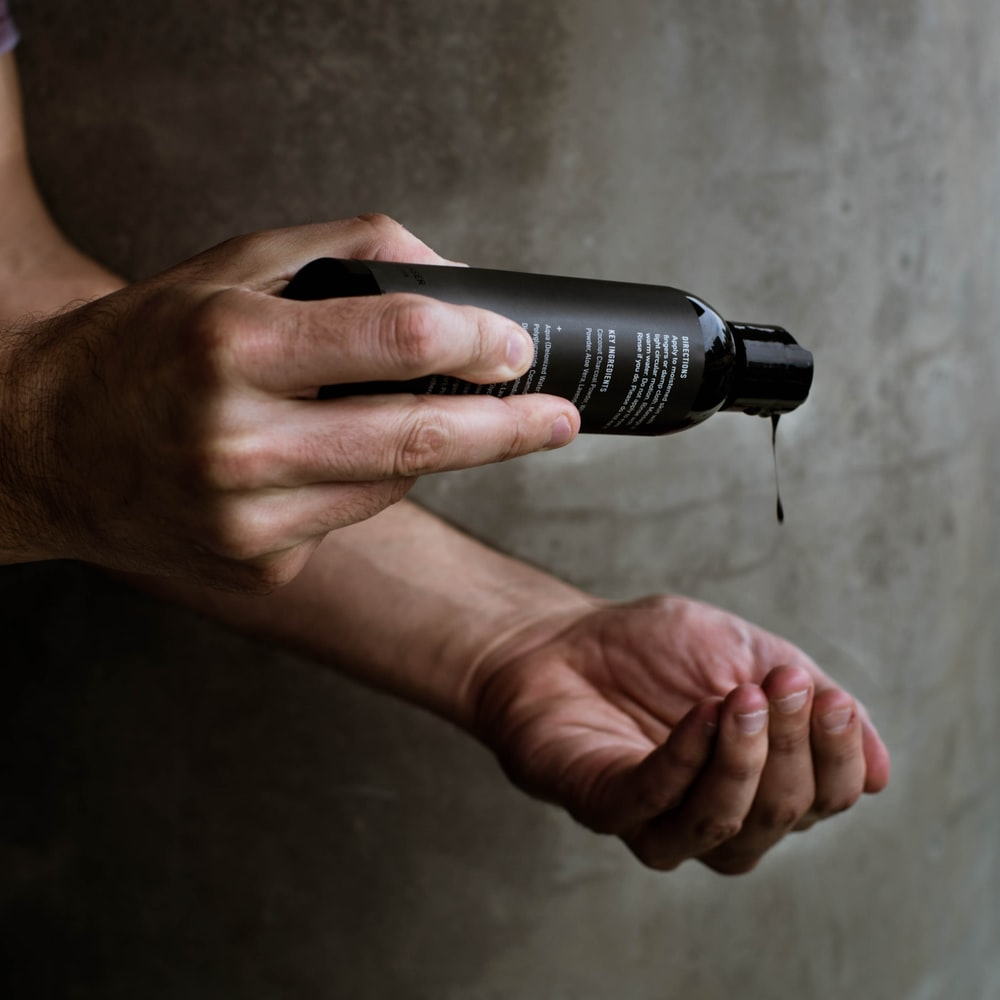 person holding black and silver flashlight