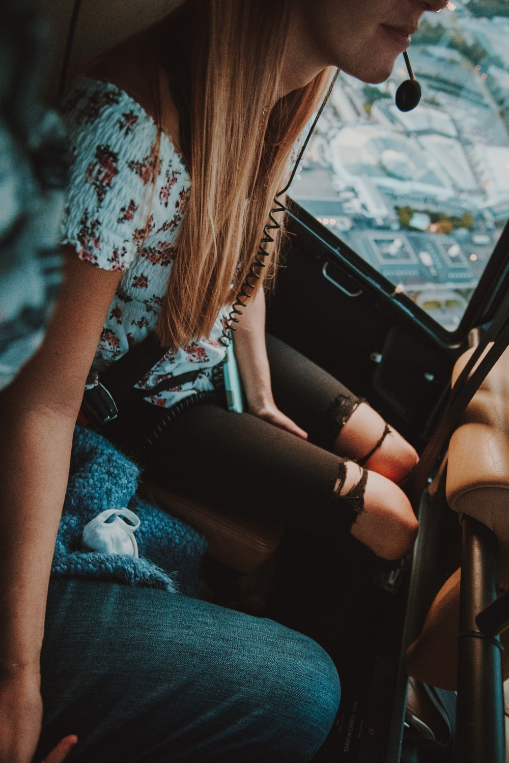 woman in white and red floral shirt sitting on car seat