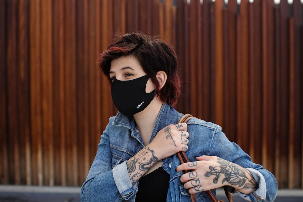 woman in blue denim jacket wearing black mask