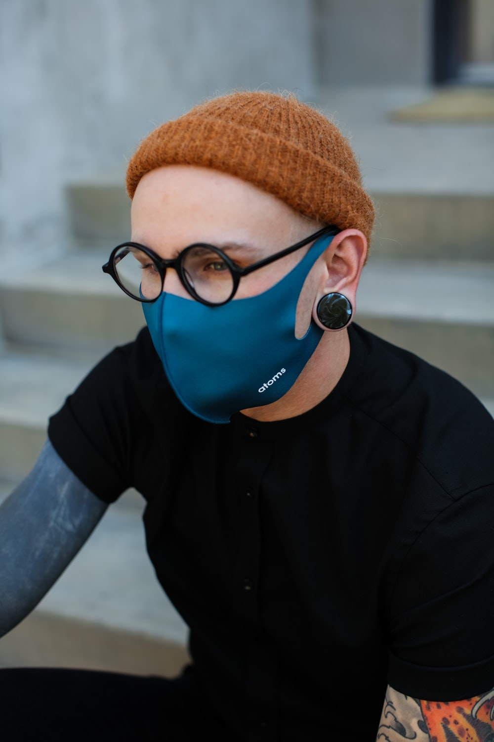 man in black button up shirt wearing brown knit cap and blue goggles