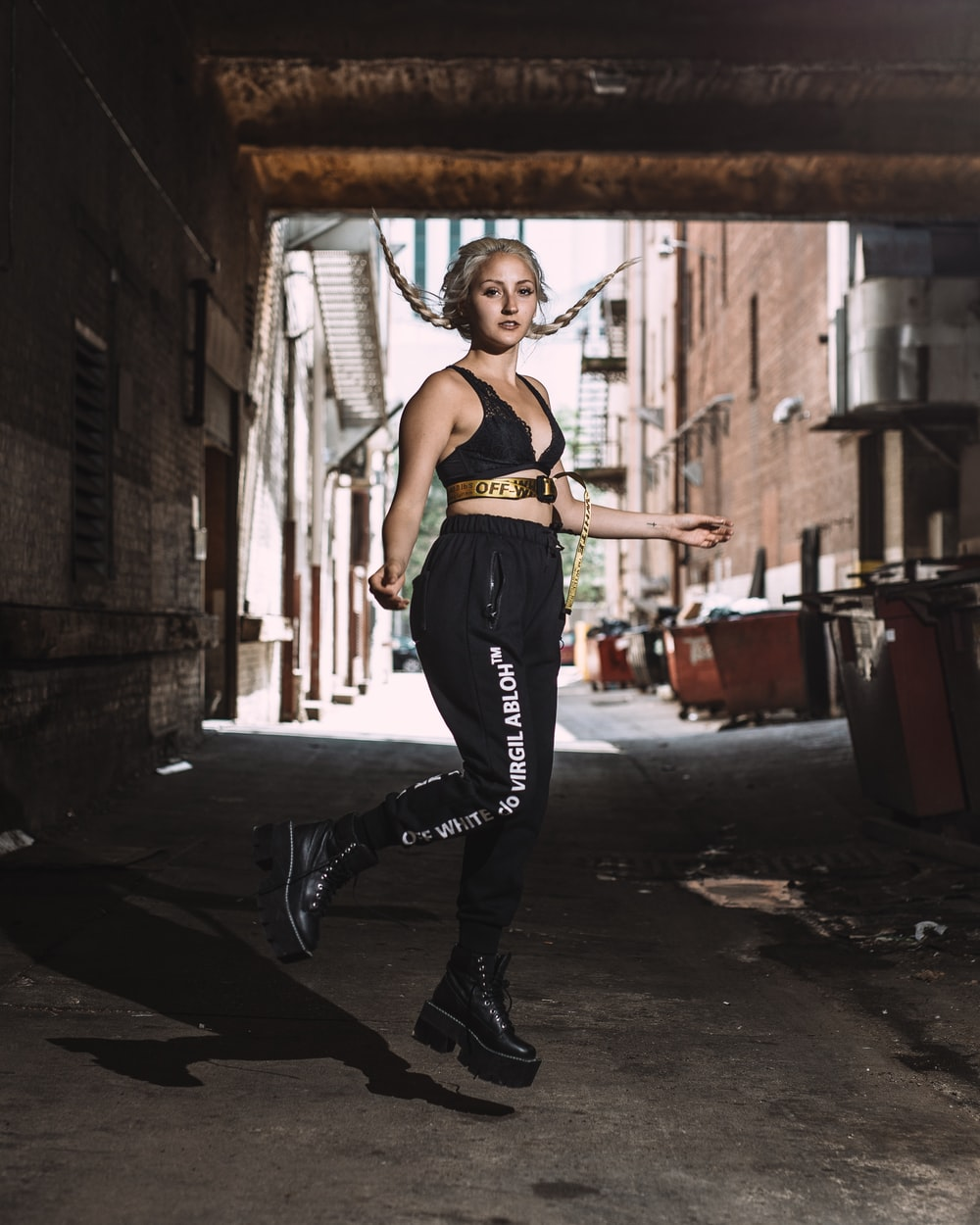 woman in black pants and black leather boots standing on black asphalt road during daytime