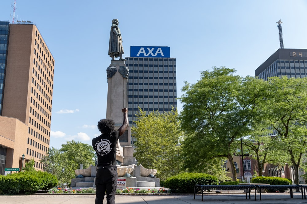 man in black and white long sleeve shirt and black pants standing near statue during daytime