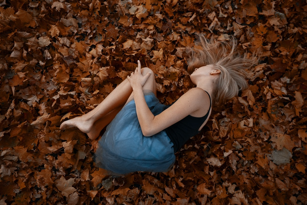 woman in blue tank top lying on dried leaves