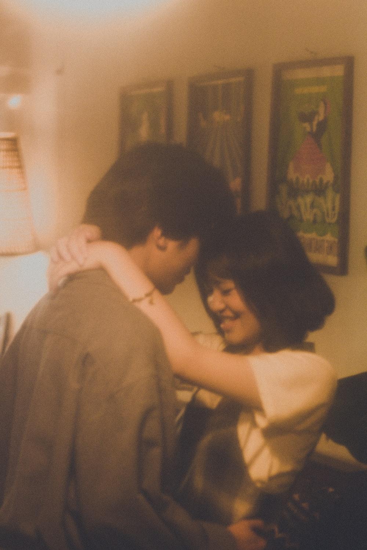 woman in white shirt hugging man in gray shirt