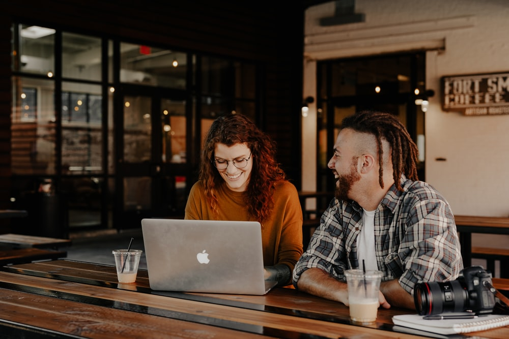 man and woman sitting at table using macbook