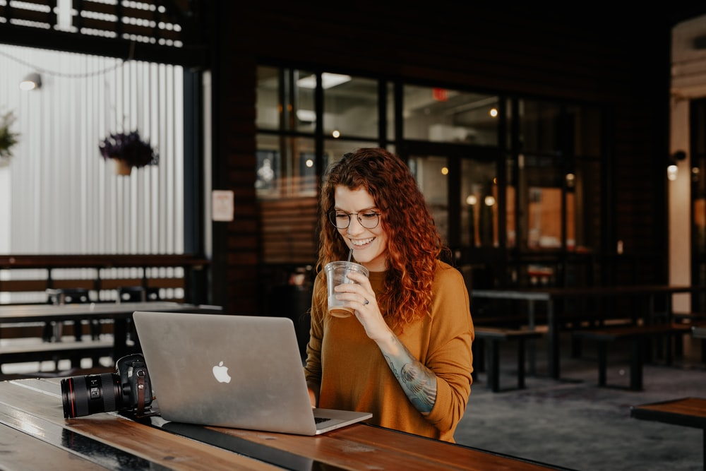 woman in brown long sleeve shirt sitting by the table using macbook