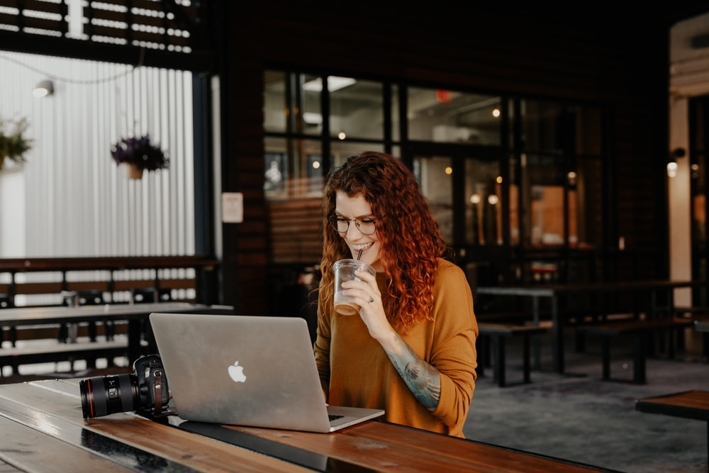 woman in orange long sleeve shirt sitting in front of silver macbook
