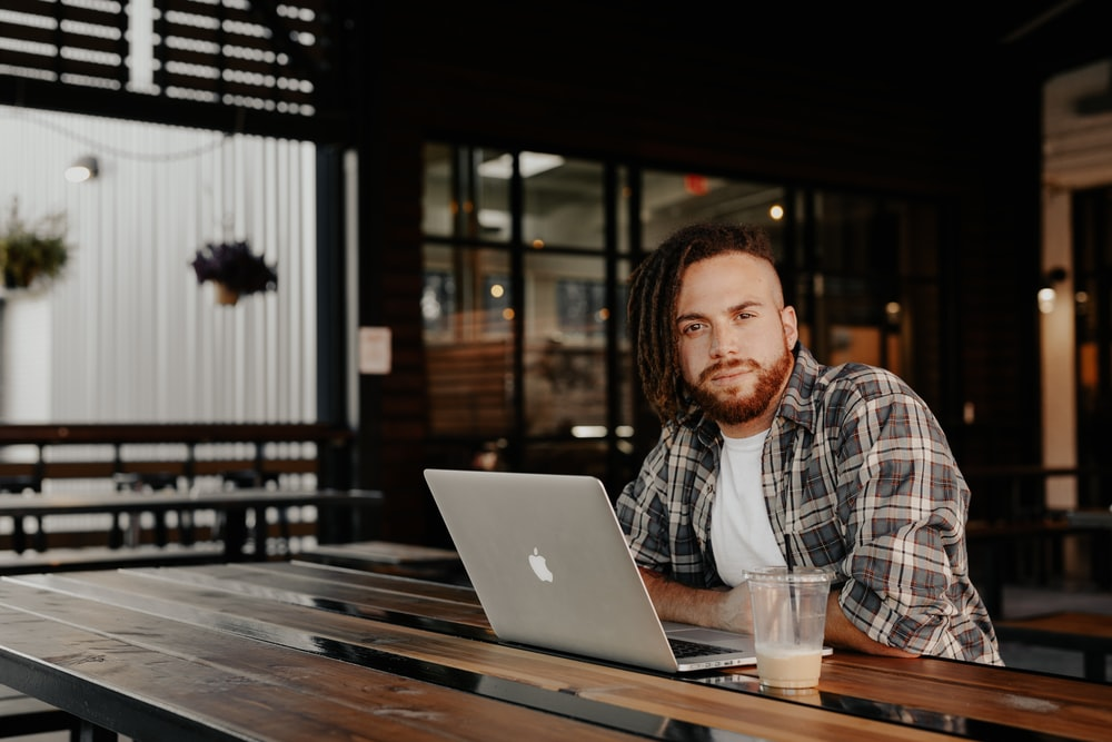 man in black and white plaid dress shirt sitting by the table using macbook