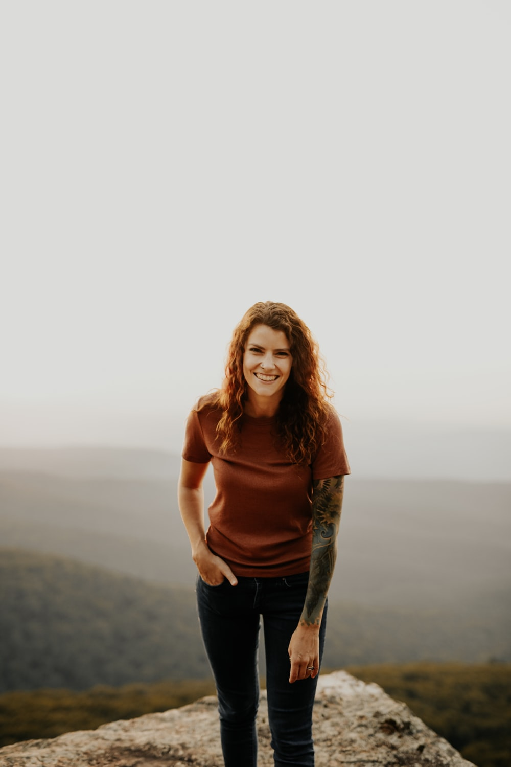 woman in brown long sleeve shirt and blue denim jeans standing on brown field during daytime