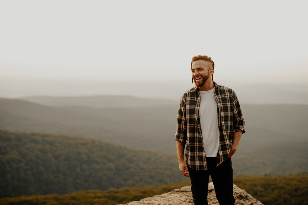 man in brown and white plaid button up shirt standing on brown rock during daytime