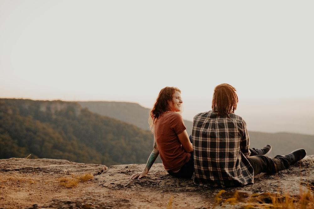 2 women sitting on rock during daytime
