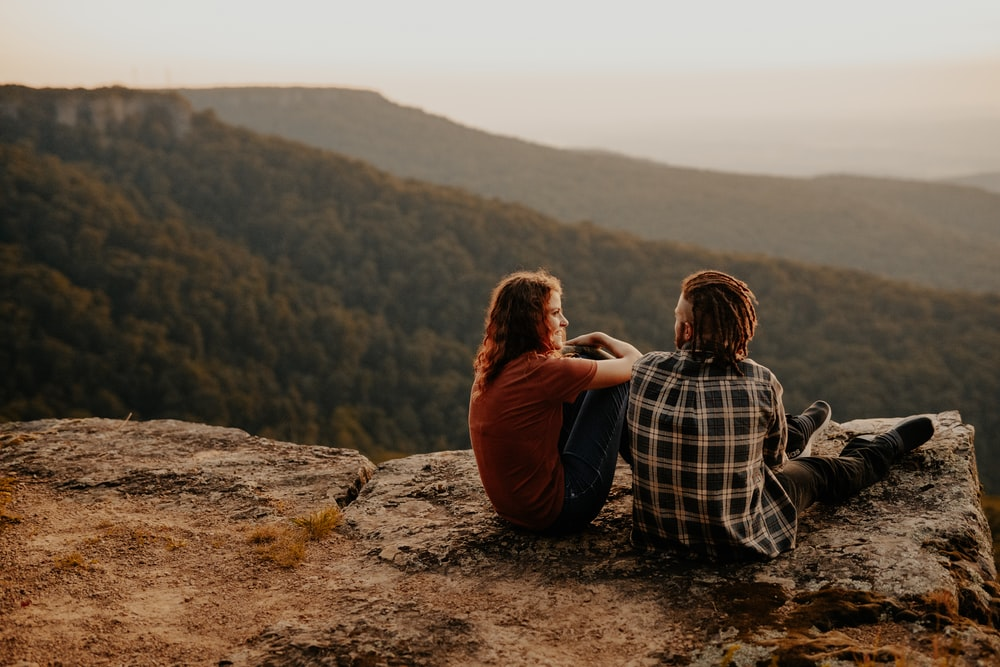 man and woman sitting on brown rock during daytime