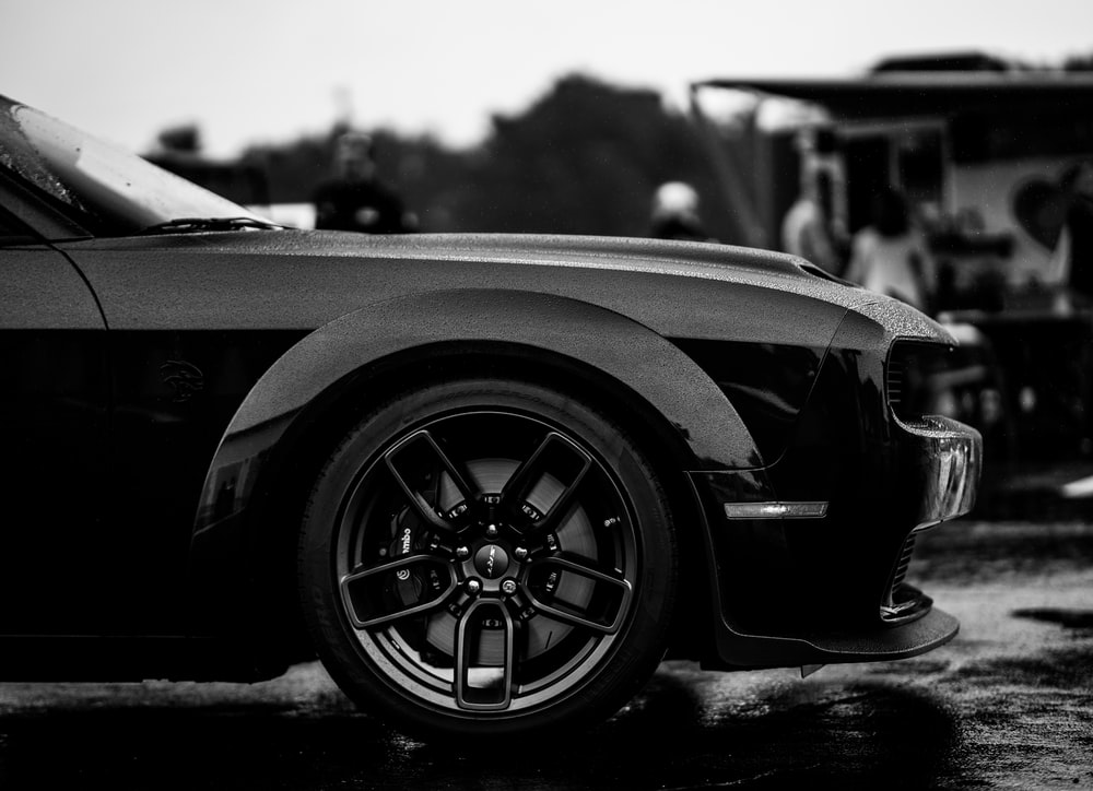 grayscale photo of car in a parking lot