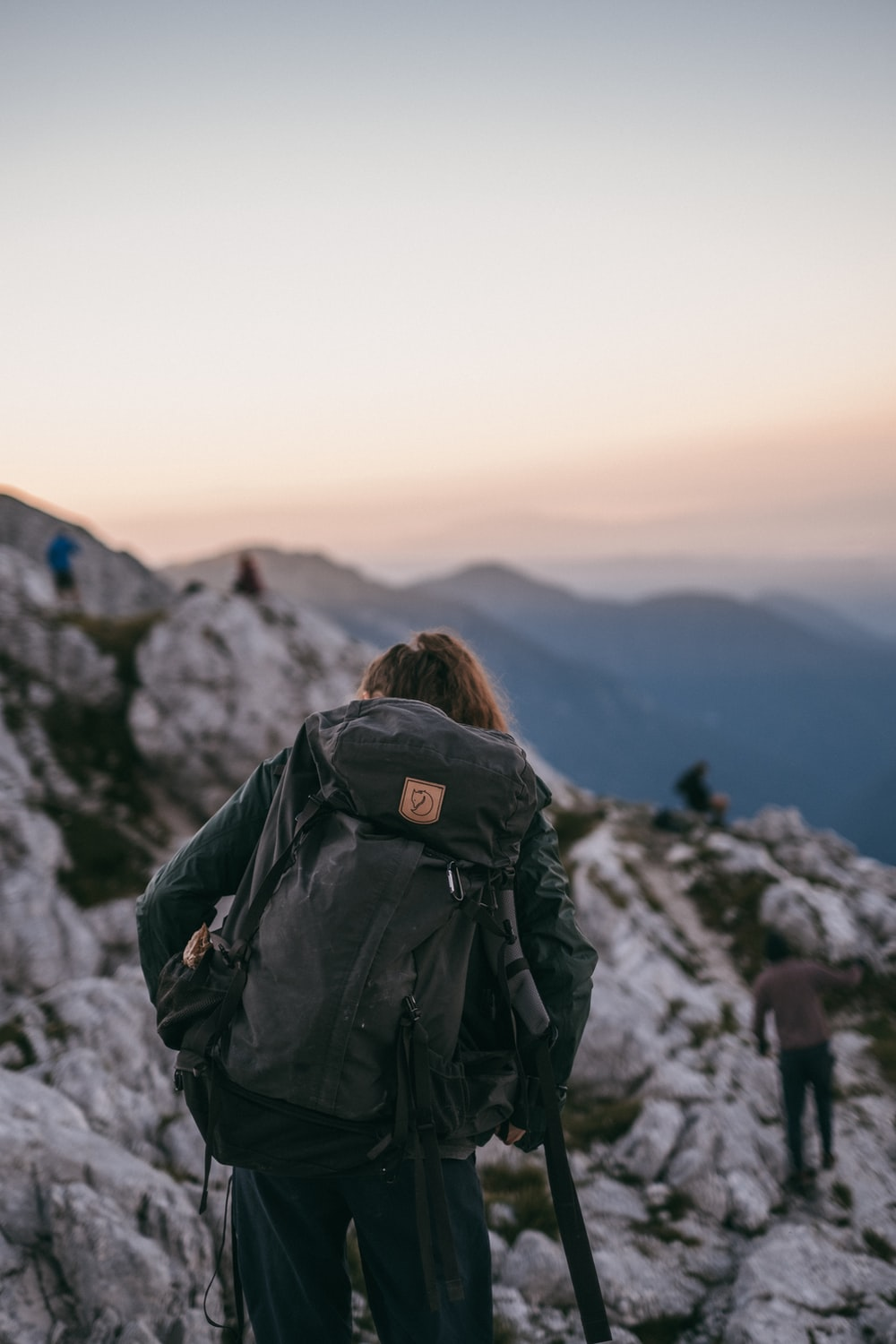 woman in black jacket with black backpack standing on mountain during daytime