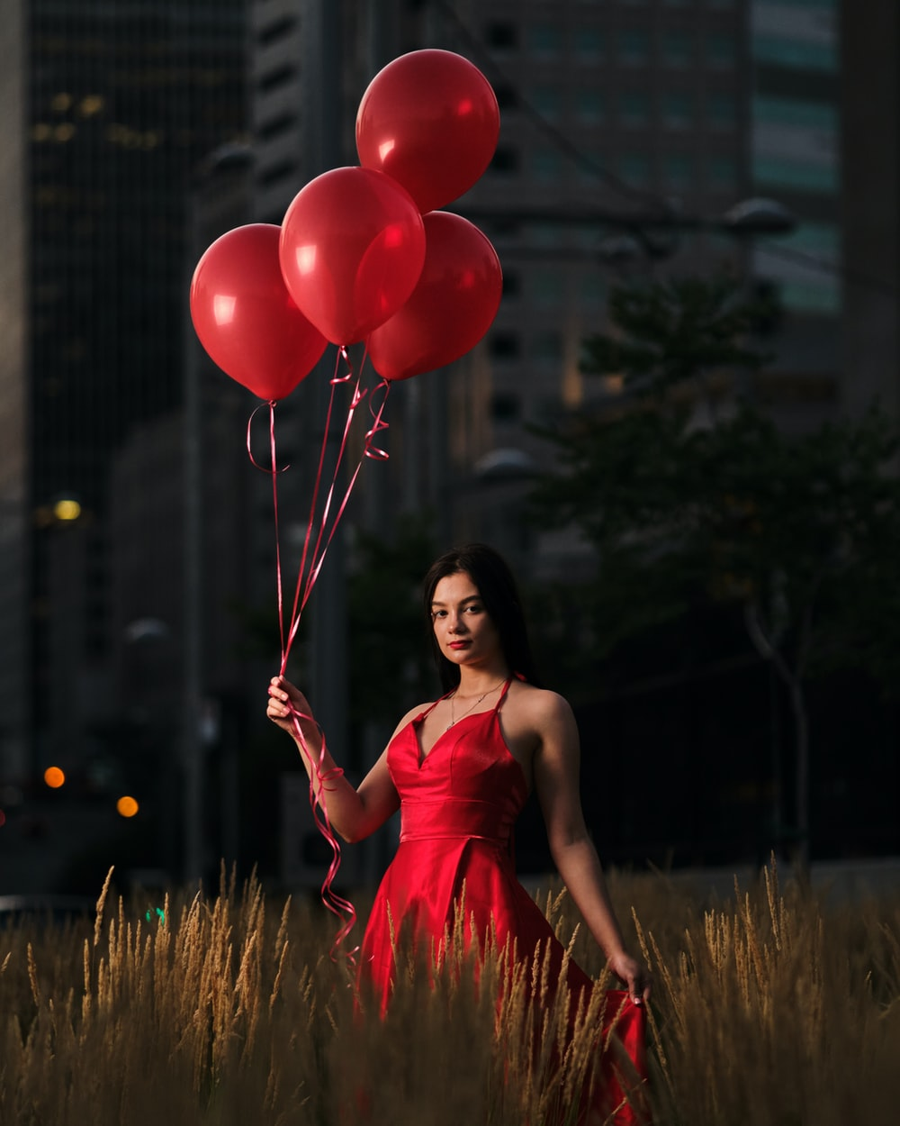 woman in pink tank top holding balloons
