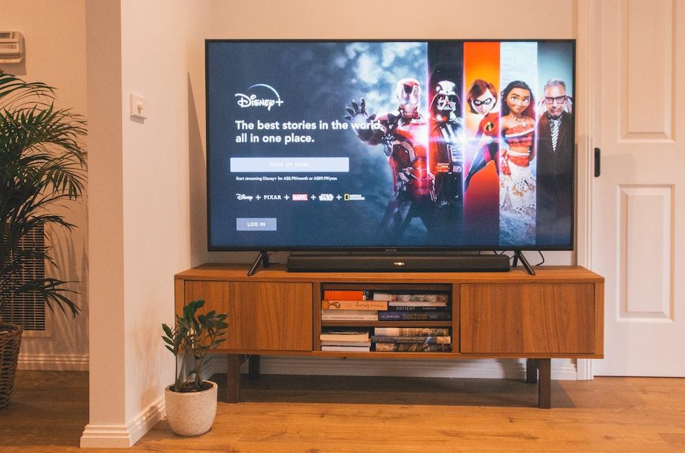 black flat screen tv turned on on brown wooden tv rack
