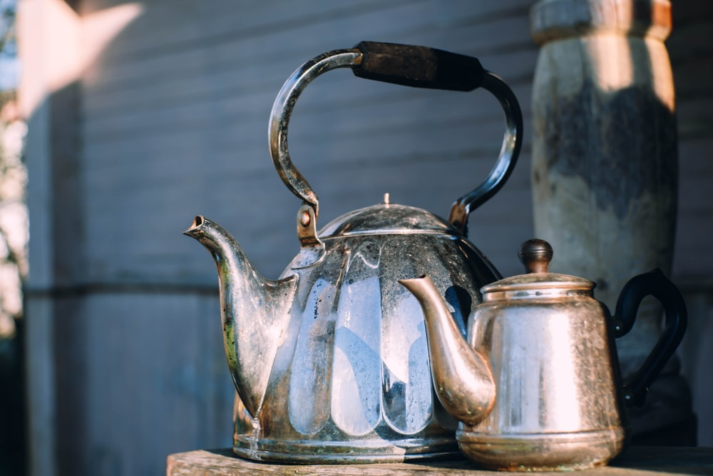 blue and silver teapot on blue table