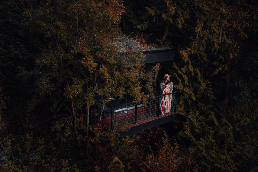 woman in red and white plaid dress shirt standing on brown wooden bridge