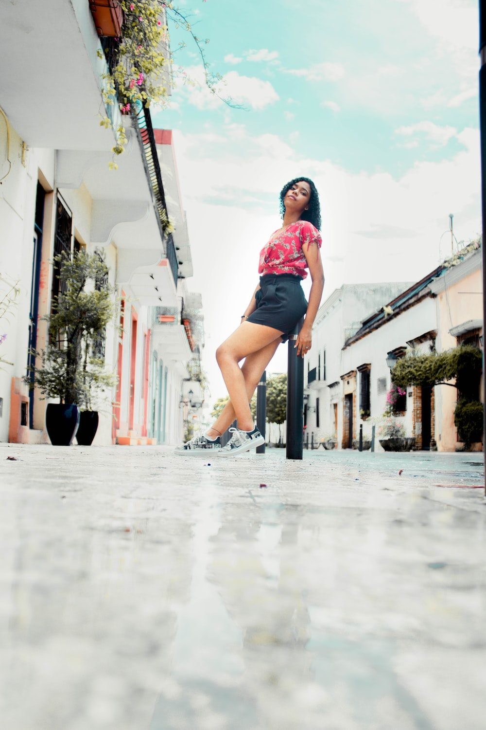 woman in pink shirt and black shorts standing on sidewalk during daytime