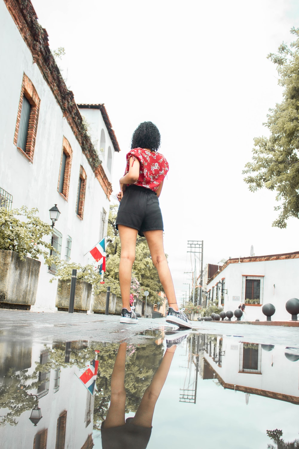 woman in red shirt and black shorts standing on water fountain