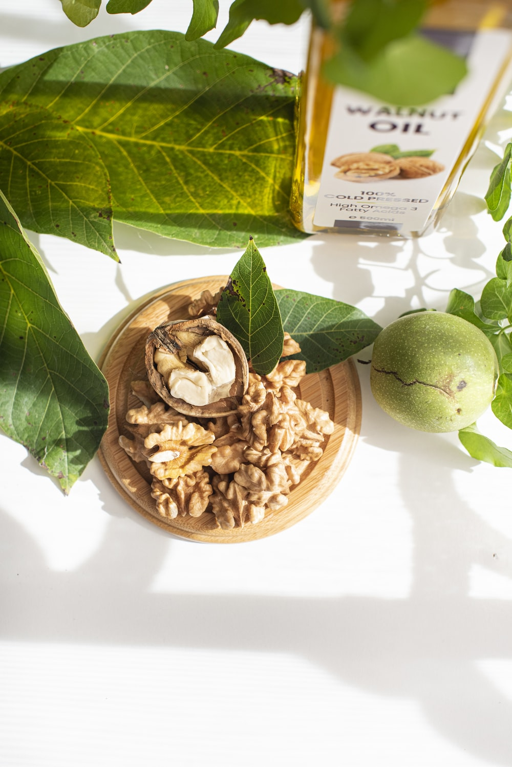 green round fruit beside brown nuts on white ceramic bowl