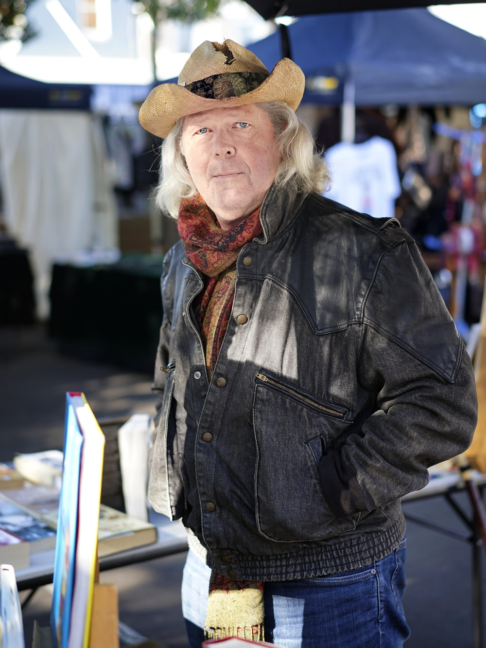 man in black leather jacket and brown cowboy hat