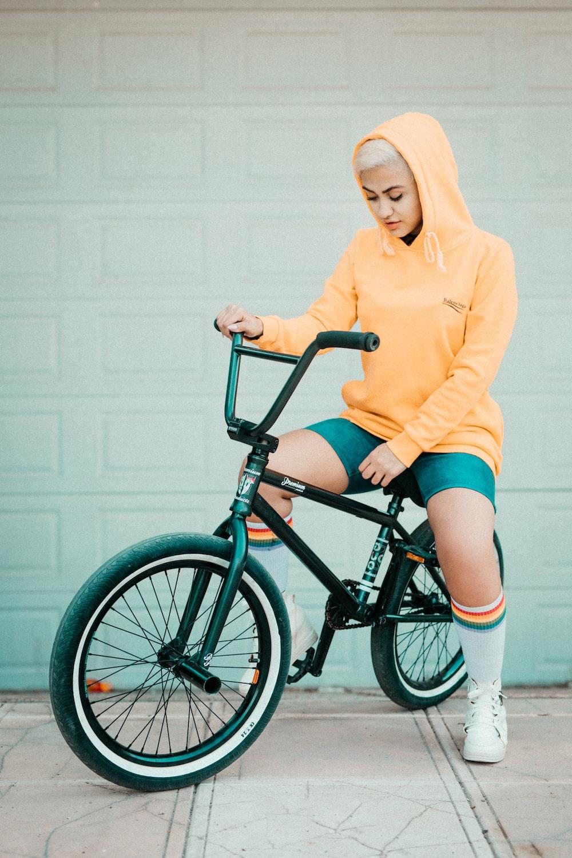 woman in yellow sweater riding black bmx bike