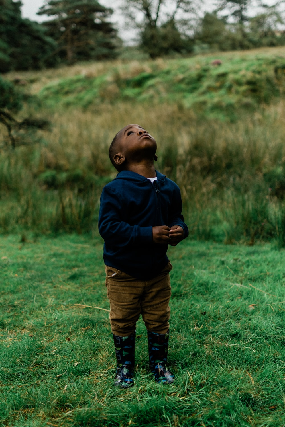 boy in blue hoodie and brown pants standing on green grass field during daytime