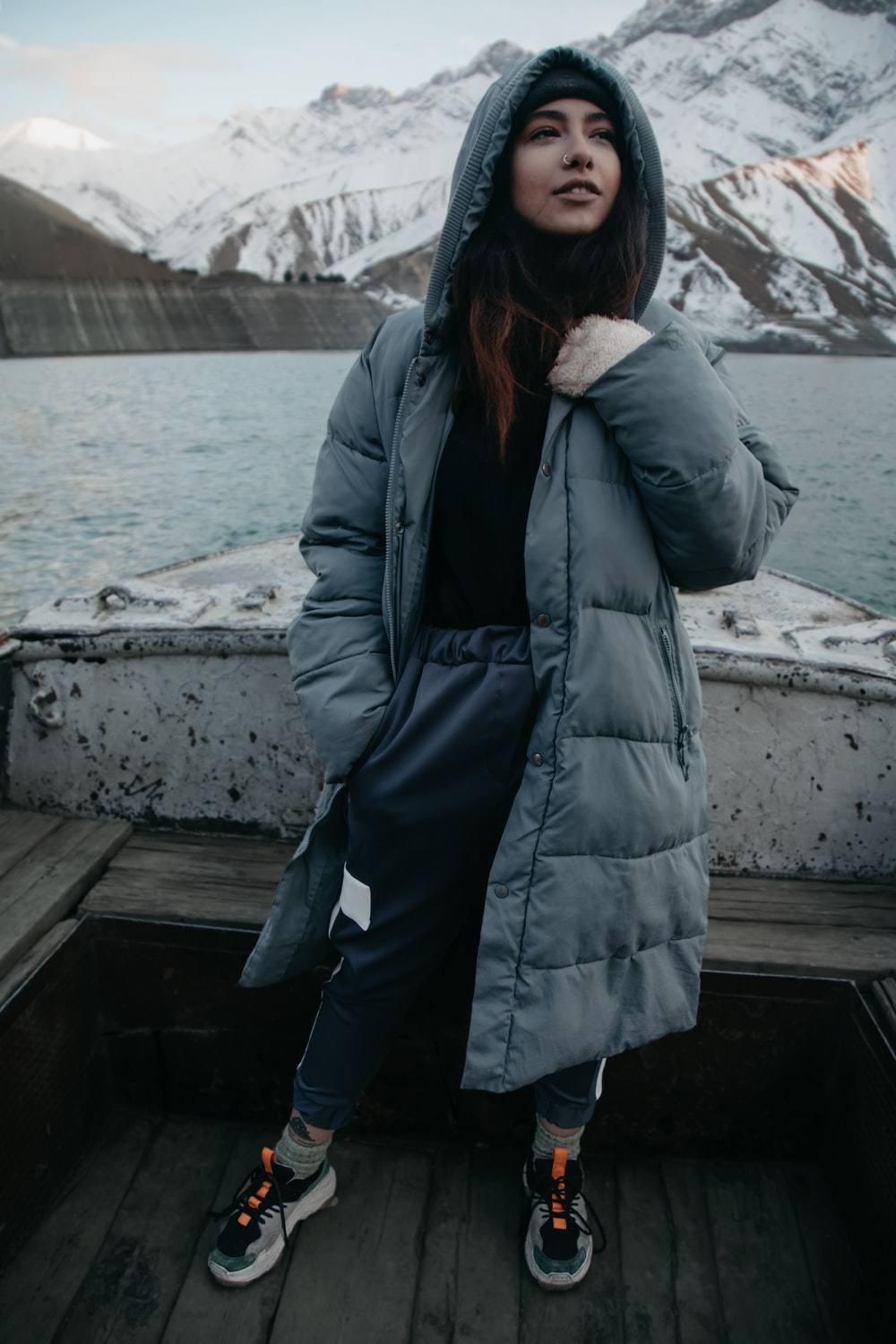 woman in black jacket standing on wooden dock during daytime