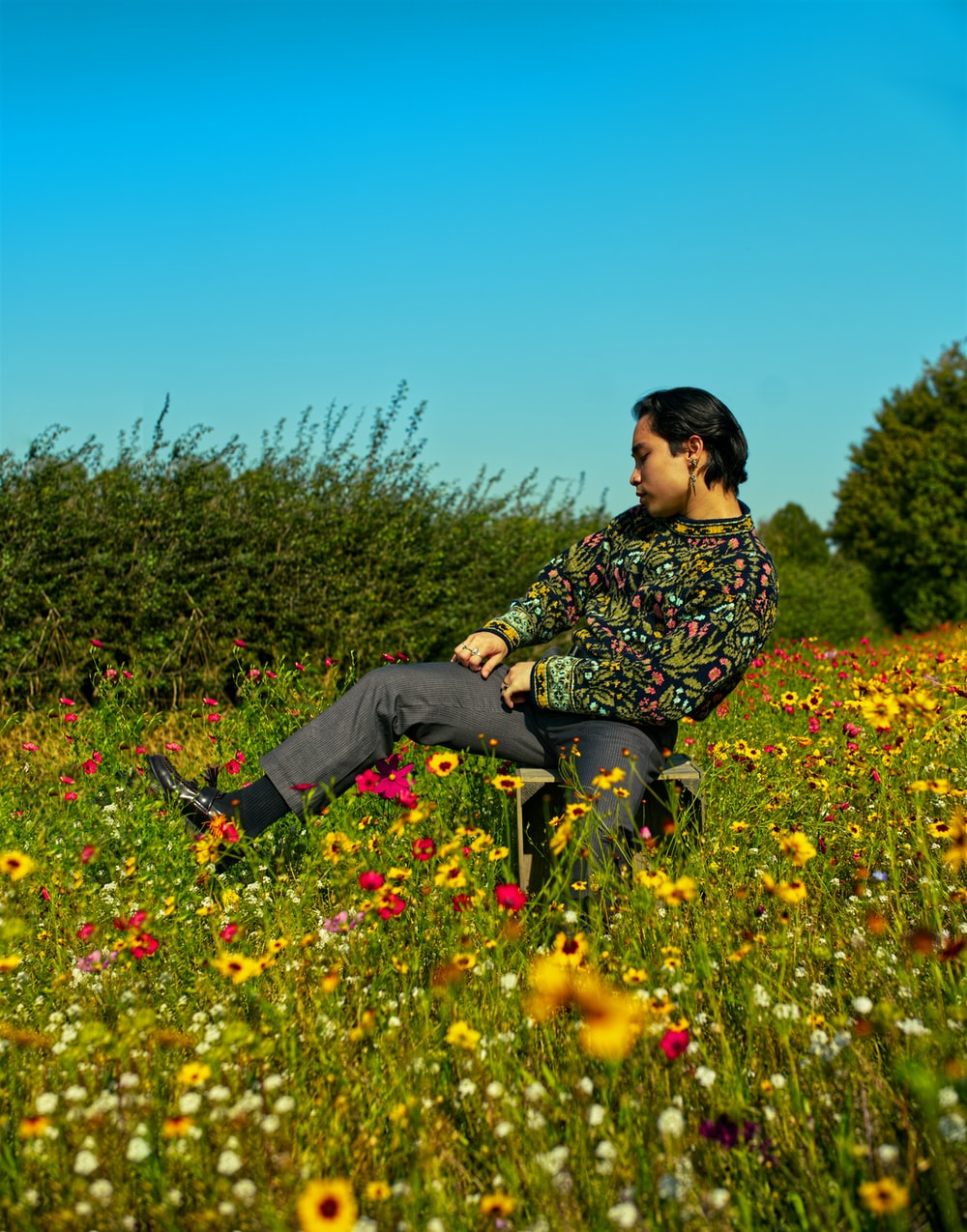 man in black and white floral long sleeve shirt sitting on yellow flower field during daytime