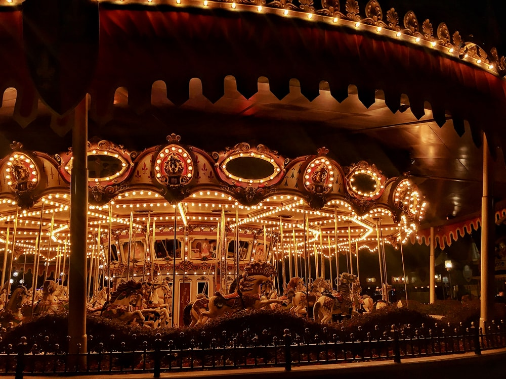 brown wooden carousel with lights turned on during night time