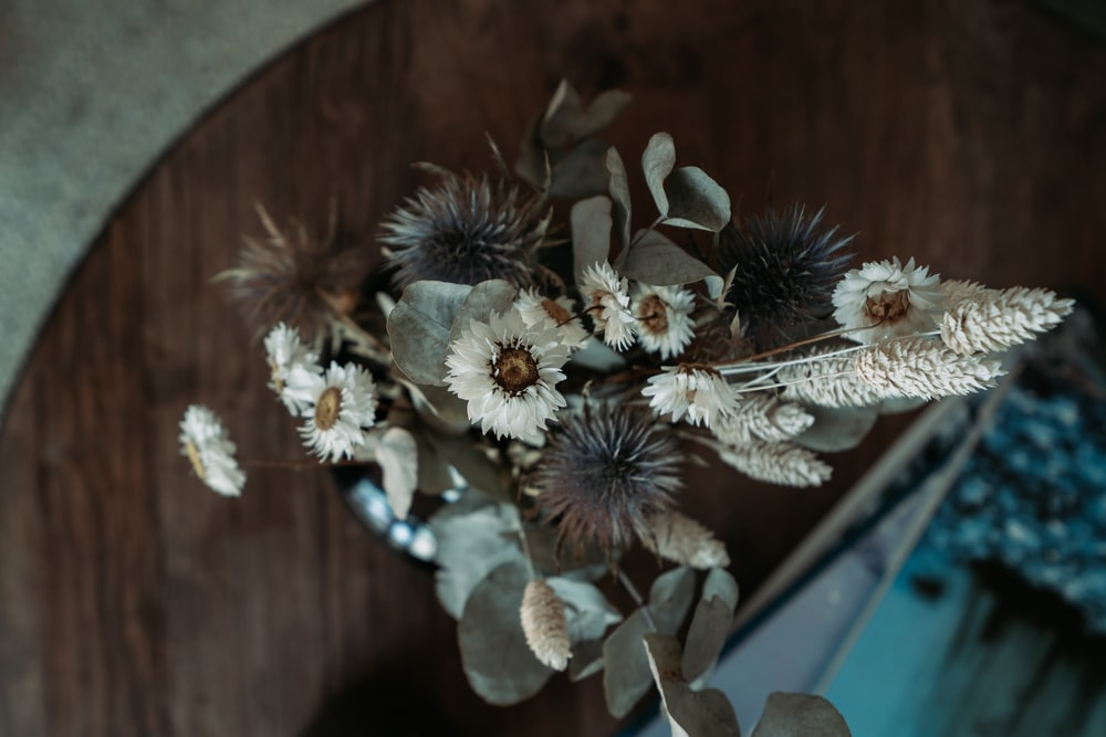 white and brown flowers on brown wooden table