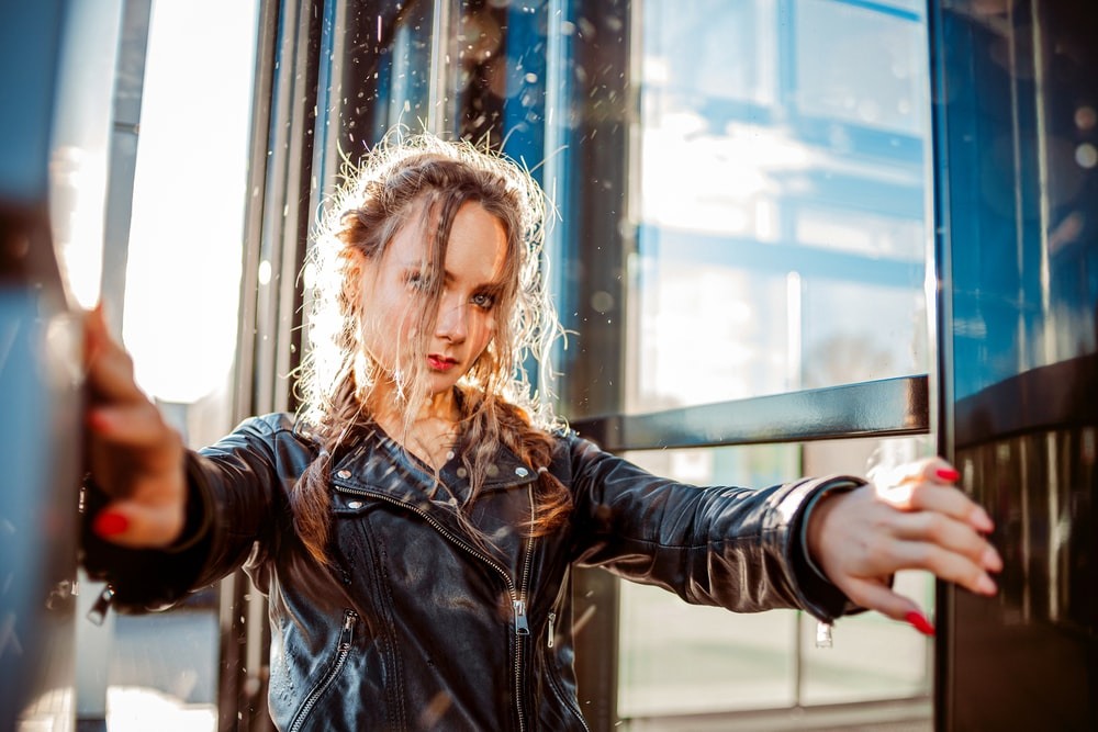 woman in black leather jacket standing near glass window during daytime