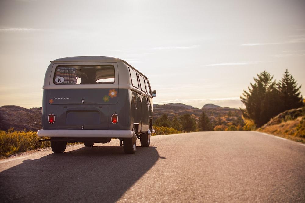 blue van on brown dirt road during daytime