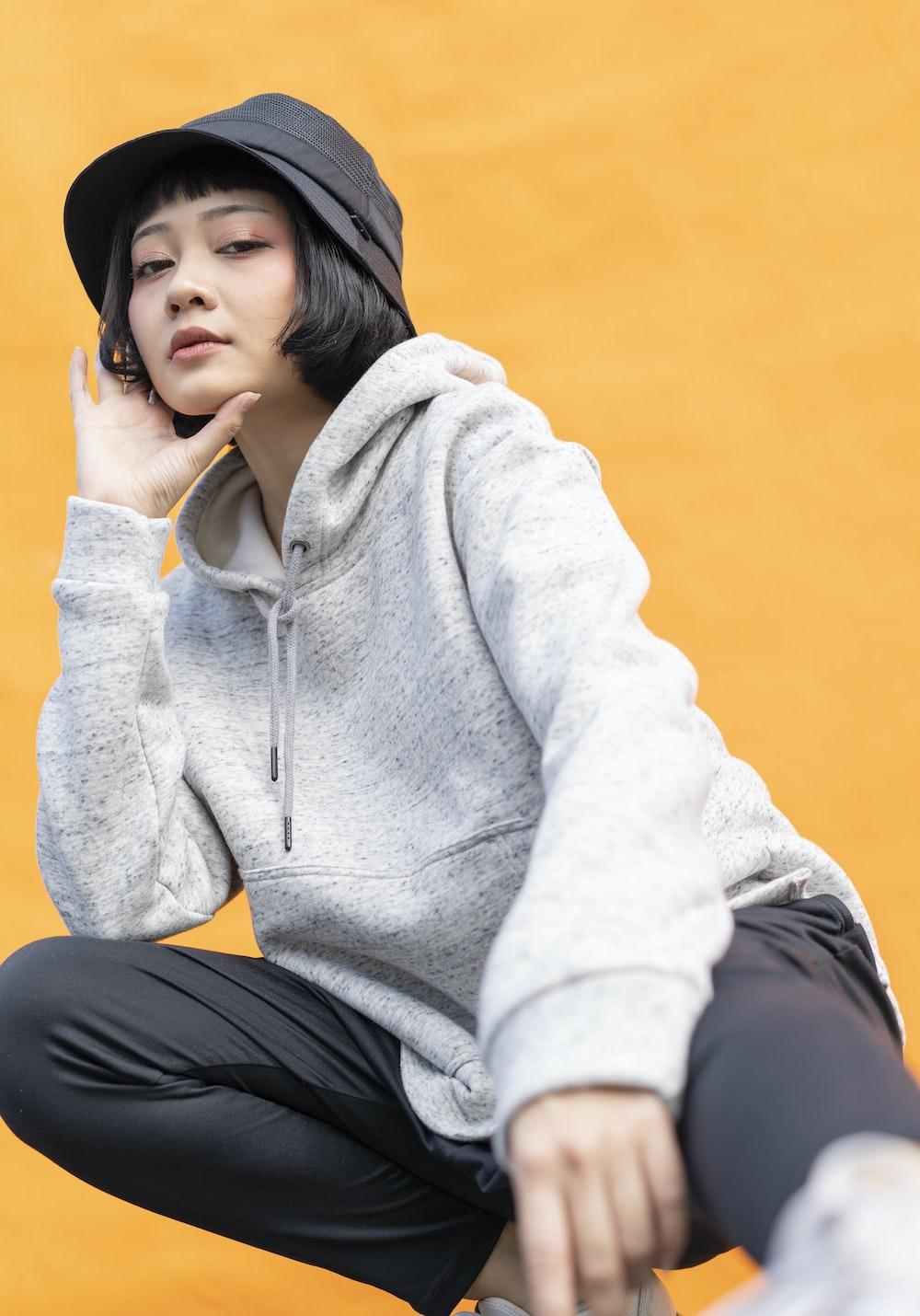 woman in gray hoodie and black pants sitting on brown wooden floor