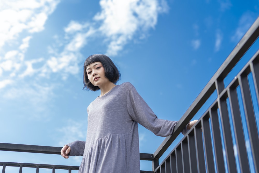 woman in gray long sleeve shirt standing beside railings under blue sky during daytime