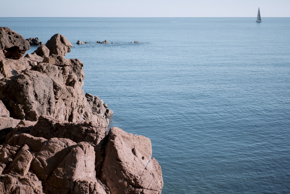 brown rocky mountain beside blue sea during daytime