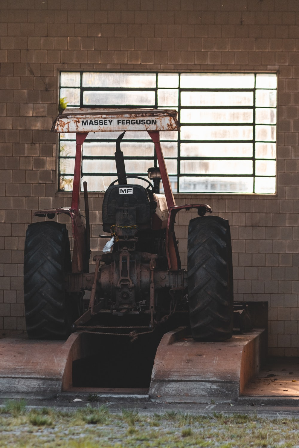 red and black tractor in front of white brick wall