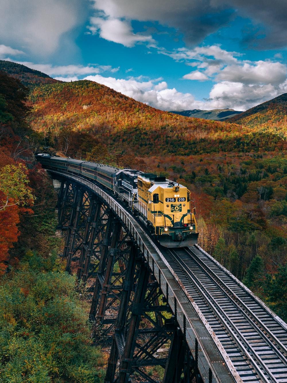 yellow train on rail tracks during daytime