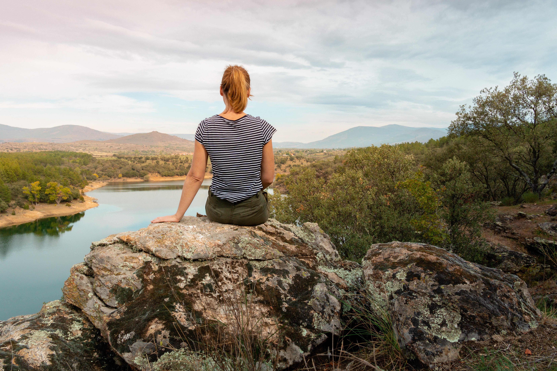 woman in black and white stripe shirt sitting on rock near lake during daytime