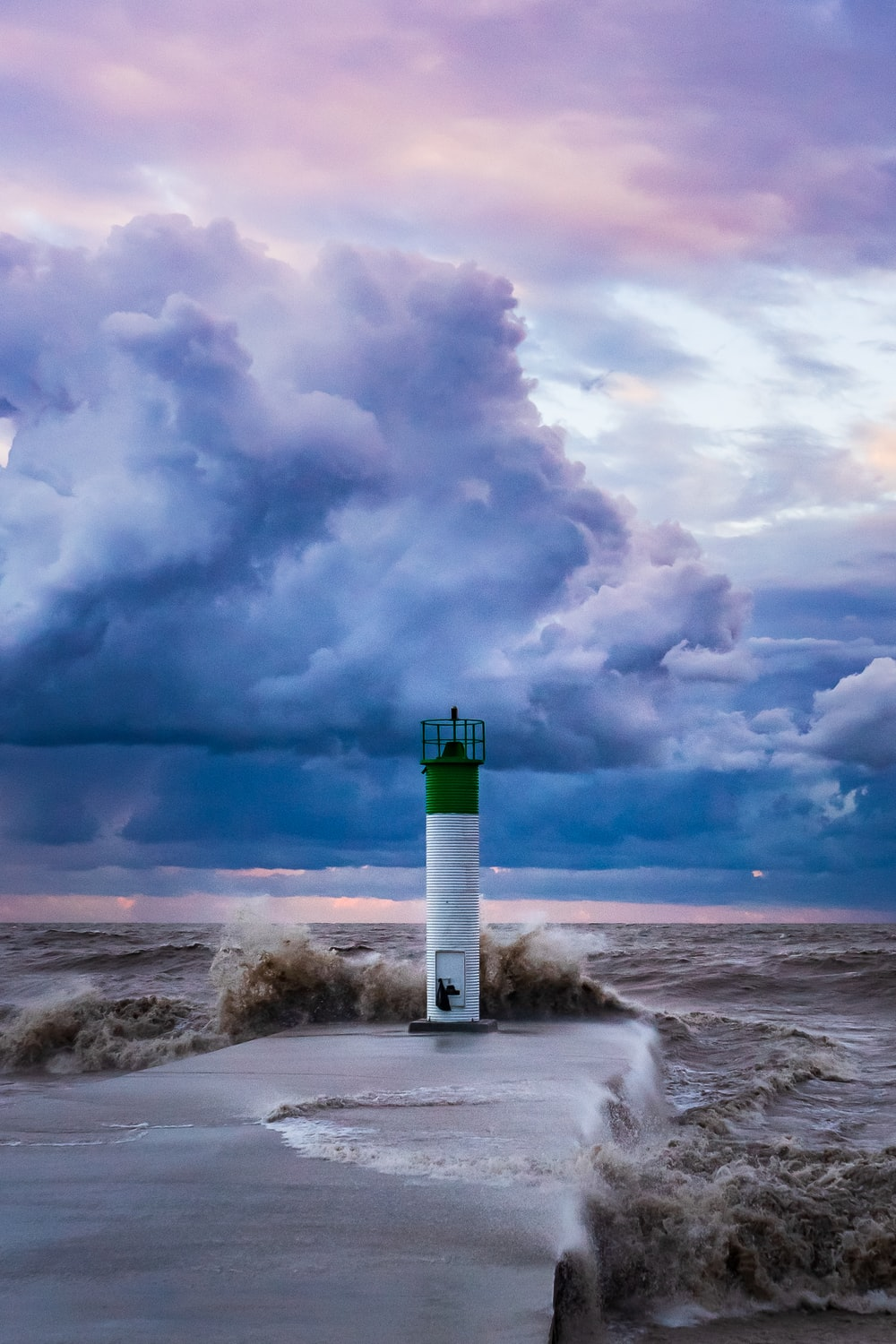 white and green lighthouse under white clouds and blue sky during daytime