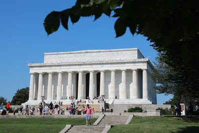 people walking in front of white concrete building during daytime lincoln memorial teams background