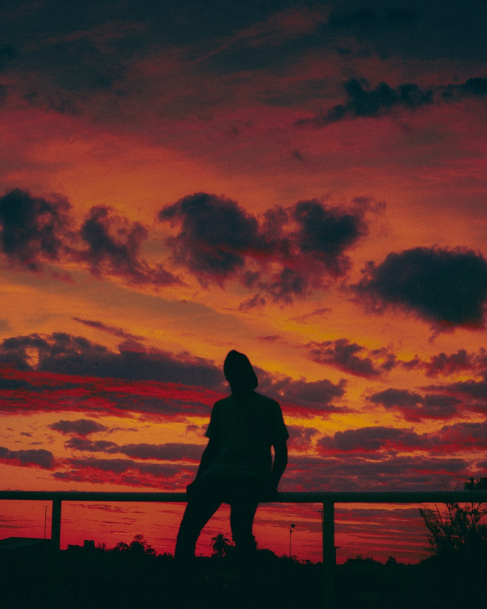 silhouette of man standing on wooden dock during sunset