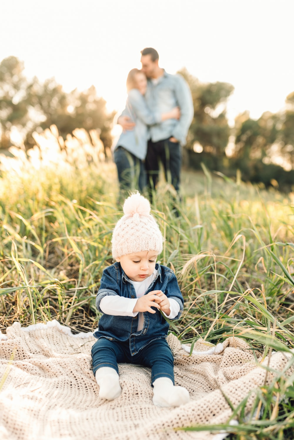 child in blue denim jacket and white knit cap sitting on white textile during daytime