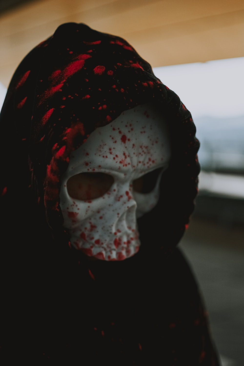 person wearing white mask and red and black scarf