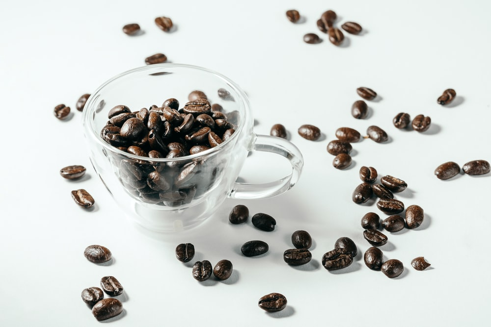 black and brown coffee beans on white ceramic cup