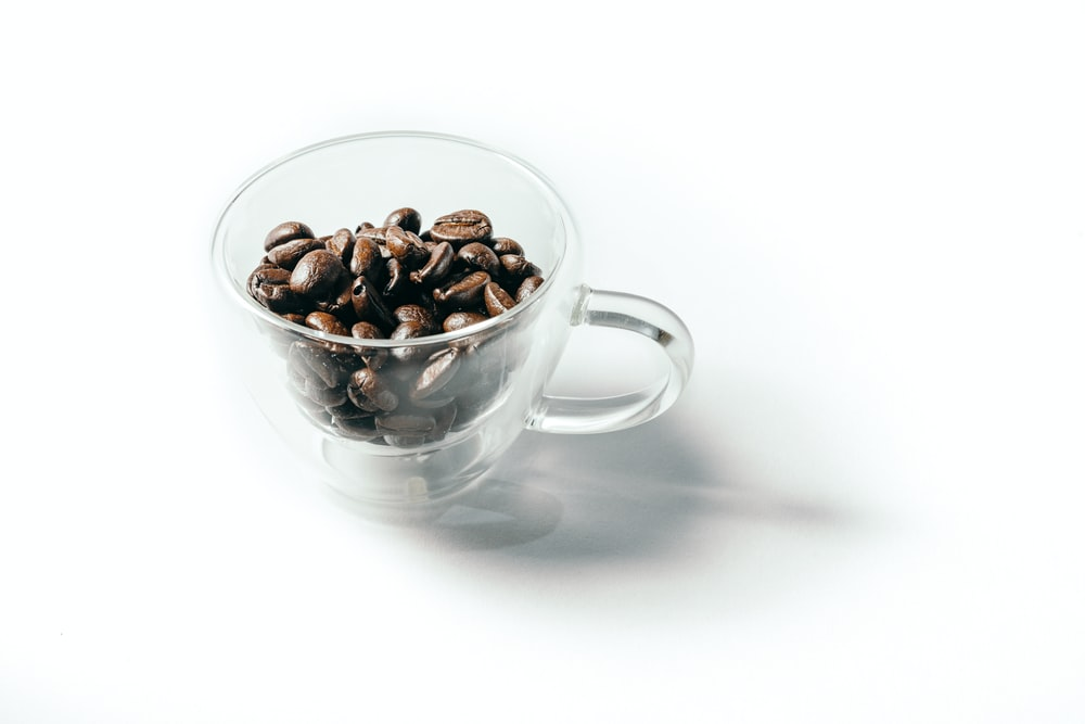 clear glass teacup with coffee beans