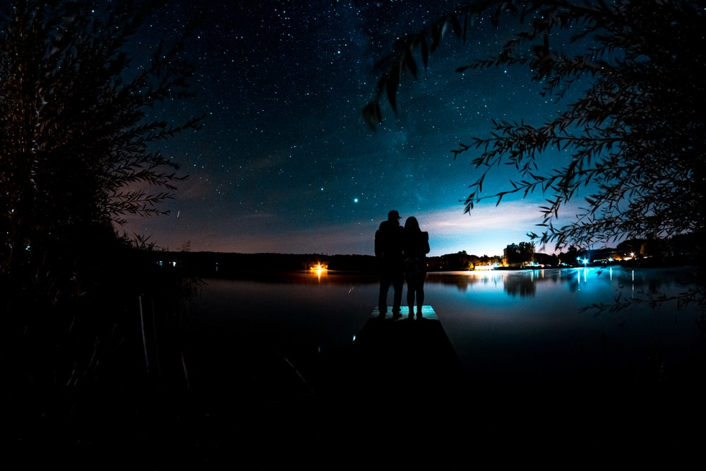 silhouette of man and woman standing on dock during night time