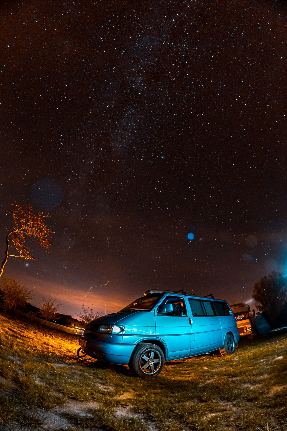 blue suv on brown grass field during night time
